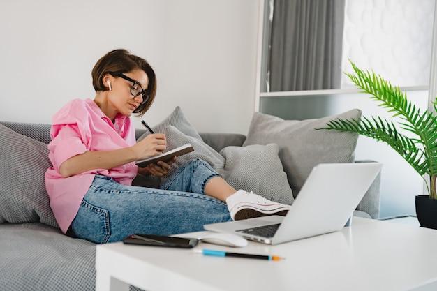 Mulher séria e atraente e ocupada com camisa rosa sentada concentrada, fazendo anotações, pagando contas no sofá em casa, à mesa, trabalhando online no laptop