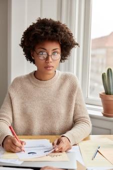 Mulher séria e atraente trabalhando em casa