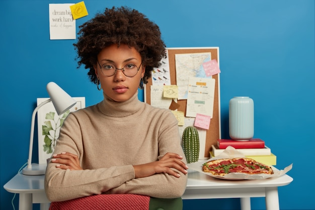 Mulher séria e autoconfiante com cabelo afro, mantém as mãos cruzadas, inclina-se na cadeira, trabalha em projeto científico em casa, faz intervalo para lanche e descanso, posa contra a mesa com livros, anotações, luminária