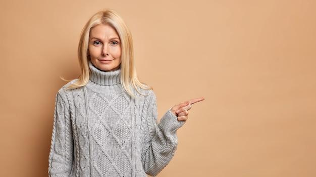 Mulher séria e autoconfiante com cabelo loiro apontando para o espaço da cópia