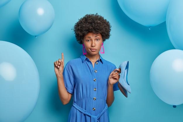 Mulher séria e confiante acima convida você para subir segurando sapatos novos em vestidos de salto alto com roupas da moda, experimenta roupas para sair, posa contra parede azul com balões