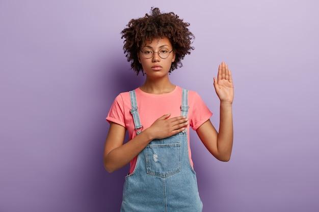 Mulher séria e confiante com cabelo encaracolado faz promessa ou juramento sincero, mantém uma mão no coração
