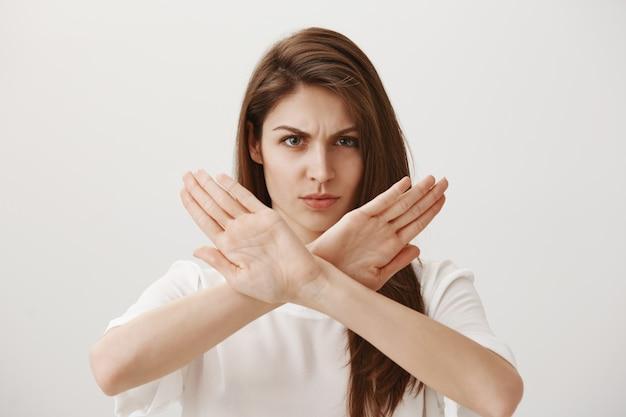 Mulher séria e confiante faz gestos zangados para recusar ou impedir alguém