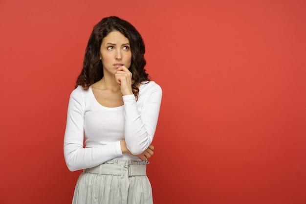 Mulher séria e duvidosa olha para cima, pensa pensativa, confusa, jovem, preocupada, chateada, mordida, lábio, em dúvida