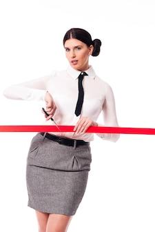 Mulher séria e focada cortando uma fita vermelha