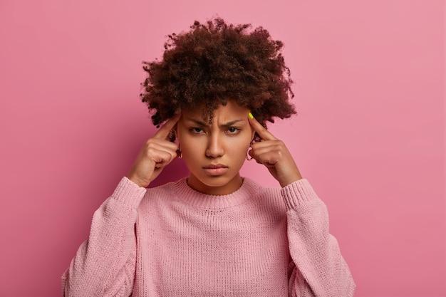 Mulher séria e intensa da américa africana concentra-se na tarefa, pensa profundamente, mantém os dedos indicadores nas têmporas, sofre de dor de cabeça ou enxaqueca, parece com expressão sombria, usa macacão casual