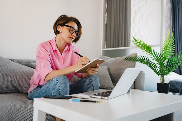 Mulher séria e ocupada com camisa rosa sentada concentrada, fazendo anotações, pagando contas no sofá em casa, à mesa, trabalhando online no laptop de casa