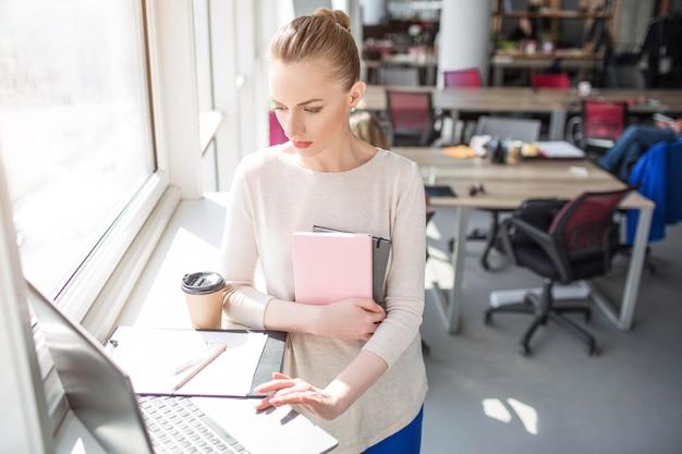 Mulher séria e ocupada está olhando para o laptop e usá-lo. ela também tem alguns cadernos nas mãos. mulher está trabalhando.