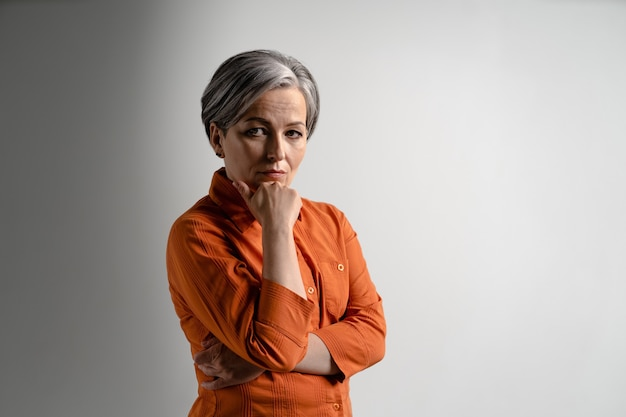 Mulher séria e pensativa de cabelos grisalhos com camisa laranja olhando para o queixo dianteiro apoiado na mão