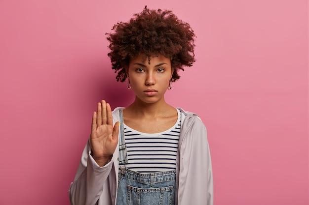 Mulher séria e rígida mostra gesto de pare, levanta a palma da mão para a frente