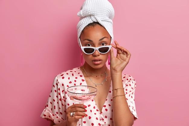 Mulher séria e terna com pele escura, parece confiante, usa óculos escuros, segura um copo de coquetel, vestida casualmente, enrolada em uma toalha no cabelo lavado, desfruta de uma atmosfera pacífica