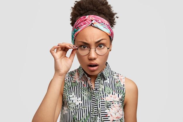 Mulher séria e zangada descontente fica desapontada ao ouvir algo desagradável e olha fixamente através de óculos redondos