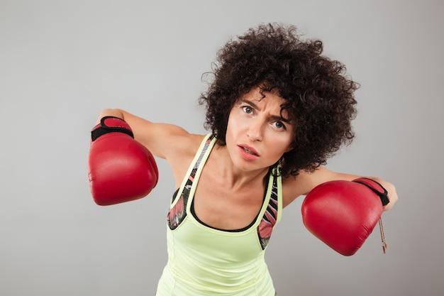 Mulher séria em luvas de boxe e olhando para a câmera