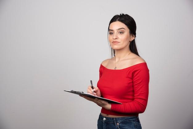 Mulher séria, escrevendo em uma prancheta e desviar o olhar.