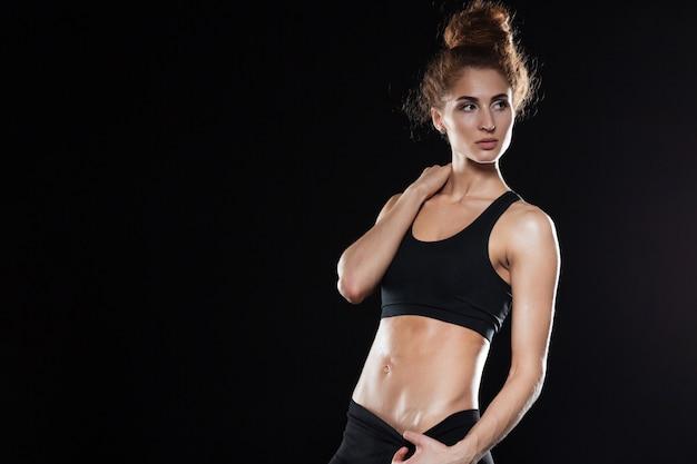Mulher séria fitness posando no estúdio