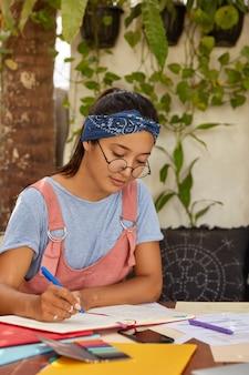 Mulher séria, mestiça, com faixa na cabeça, vestida com camiseta casual e macacão, escreve os registros no bloco de notas