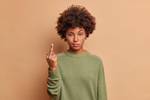 Mulher séria mostra foda-se você assina looks com cara de pau sendo vulgar e briga com alguém vestido de suéter casual isolado sobre parede bege