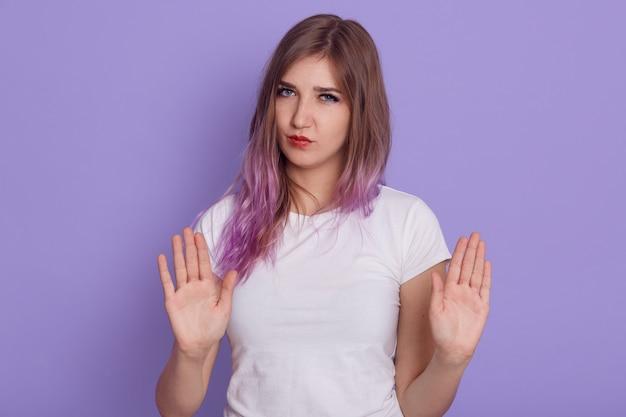 Mulher séria, mostrando as palmas das mãos para a câmera, olhando com expressão estrita e gesto de proibição, proíbe alguém de fazer coisas ruins, isoladas sobre a parede roxa.