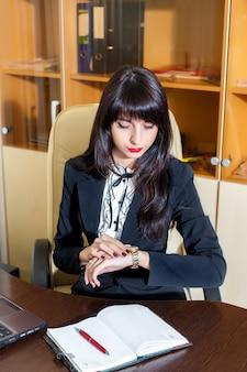 Mulher séria no escritório olhando para o relógio