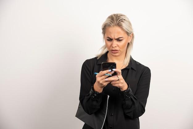 Mulher séria olhando no celular e segurando uma prancheta. foto de alta qualidade
