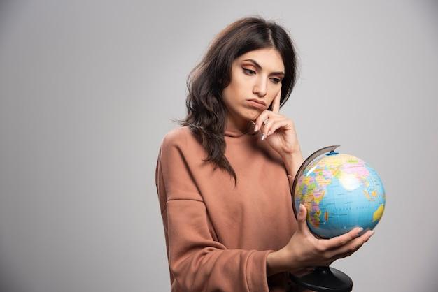 Mulher séria olhando para o globo em cinza