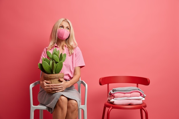 Mulher séria, pensativa, de meia-idade, usa máscara protetora e pensa na segurança durante a pandemia. segura cacto em vaso, senta-se na cadeira sozinho e fica em casa durante o período de quarentena. distanciamento social da covid 19