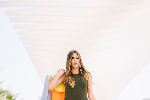 Mulher séria posando com sacolas de compras