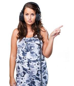 Mulher séria que escuta a música e que aponta ao copyspace