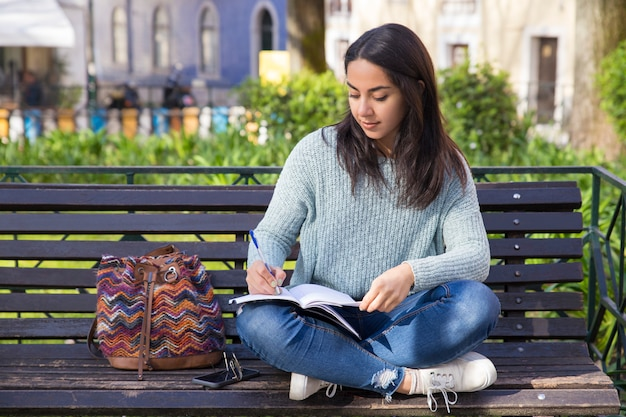 Mulher séria que faz anotações e que senta-se no banco ao ar livre