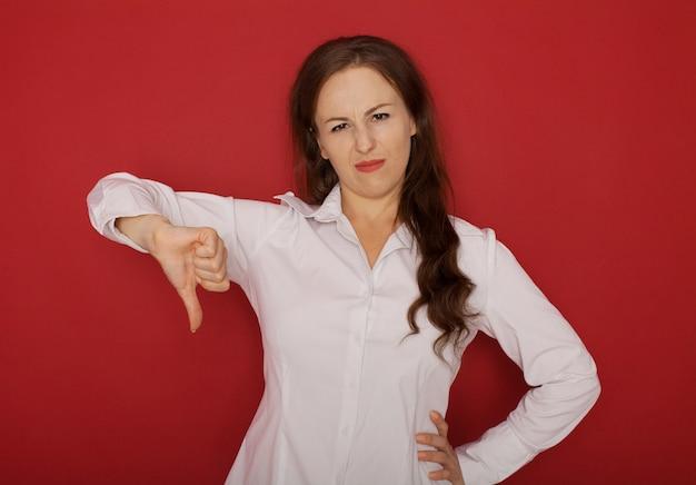 Mulher séria segura nova que gesticula o polegar para baixo