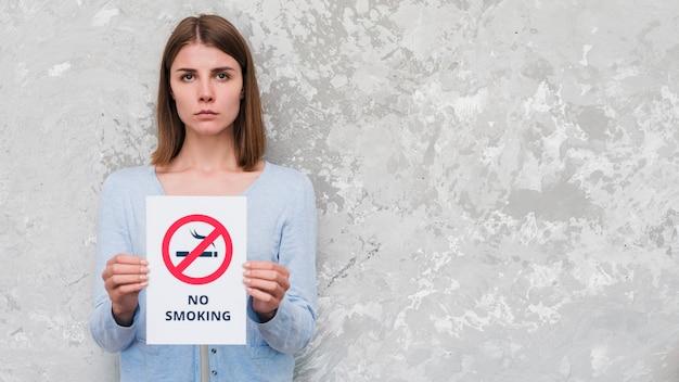 Mulher séria segurando com texto não fumar e sinal de pé contra a parede resistiu