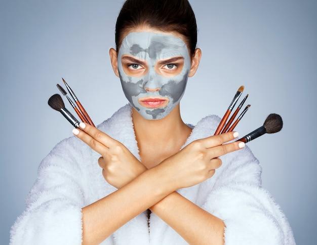 Mulher séria segurando os pincéis de maquiagem