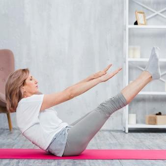 Mulher séria sênior, esticando as pernas no tapete de ioga rosa