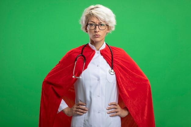 Mulher séria, super-heroína eslava em uniforme de médico com capa vermelha e estetoscópio em óculos ópticos