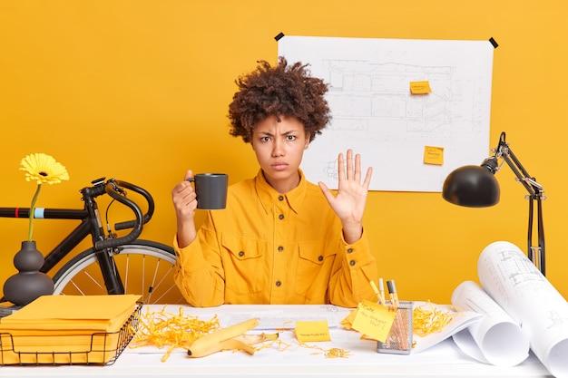 Mulher séria trabalhadora de escritório faz gesto de parada, bebe poses de café na área de trabalho bagunçada