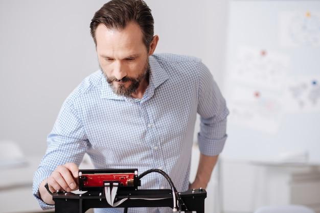 Mulher séria, trabalhadora e simpática, inclinando-se para a frente e olhando para a tela da impressora 3d enquanto verifica como ela funciona