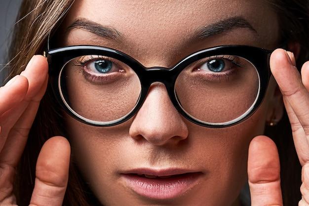 Mulher séria usando óculos de armação preta