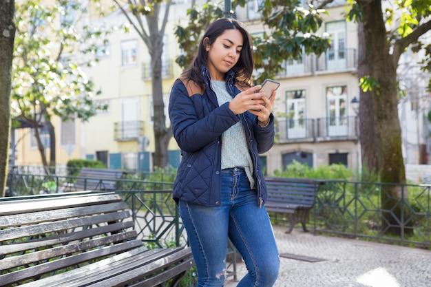 Mulher séria usando smartphone e em pé ao ar livre