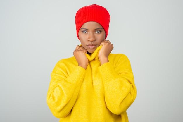 Mulher séria, vestindo blusa amarela brilhante e chapéu vermelho
