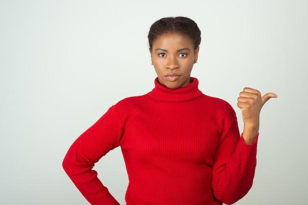 Mulher séria vestindo blusa vermelha e apontando o polegar para o lado