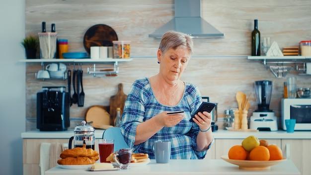 Mulher sernior usando cartão de crédito para fazer compras online na cozinha durante o café da manhã. idoso aposentado que usa o pagamento pela internet, compra do banco doméstico com tecnologia moderna