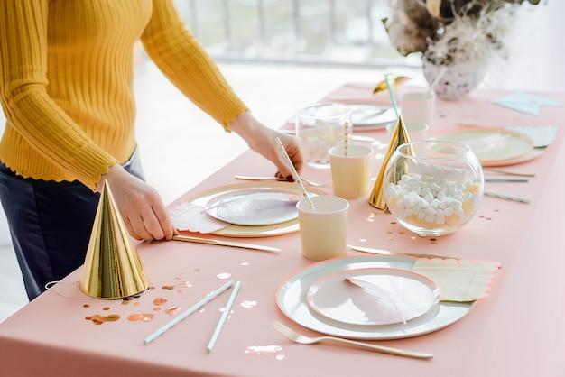 Mulher servindo a mesa de festa em tons pastel com toalha de mesa-de-rosa, pratos coloridos de papel, copos e talheres de ouro. feliz aniversário para menina.