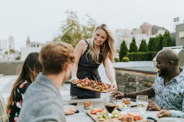 Mulher servindo churrasco vegan para seus amigos