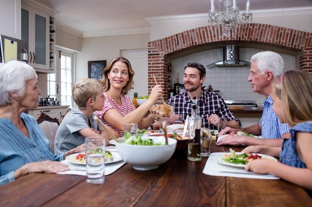 Mulher servindo comida para sua família na cozinha