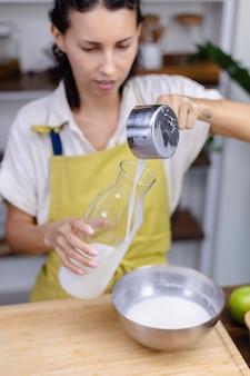 Mulher servindo leite de amêndoa em garrafa de vidro