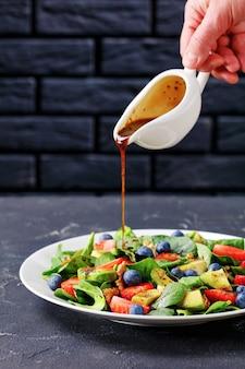 Mulher servindo molho caseiro sobre salada de espinafre, nozes, morango e mirtilo em um prato branco