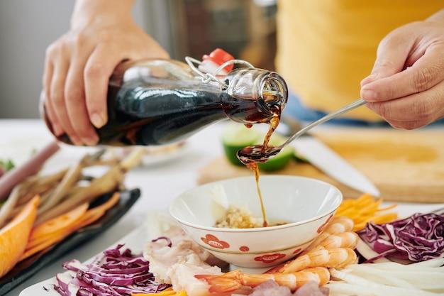 Mulher servindo molho de soja em uma tigela pequena