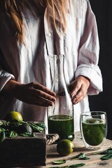 Mulher servindo smoothie verde e branco recém-misturado em uma jarra de vidro