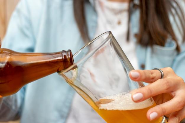Mulher servindo uma cerveja em um copo de vidro