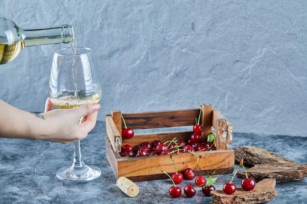 Mulher servindo vinho branco enquanto segura um copo e uma caixa de madeira com cerejas na superfície azul